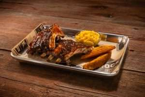 Ribs on a platter with potato wedge and Mac and cheese